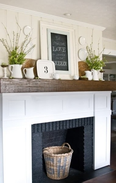 a rustic farmhouse mantel with blooming branches in jugs, decorative plates and a chalkboard