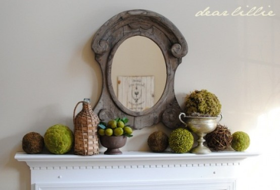 a vintage-inspired spring mantel with moss balls, fake fruit arrangement and topiaries