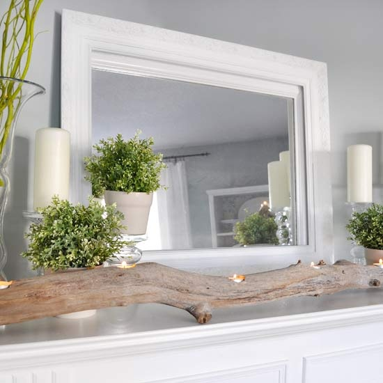 a simple and modern spring mantel with a branch with candles, potted greenery and candles