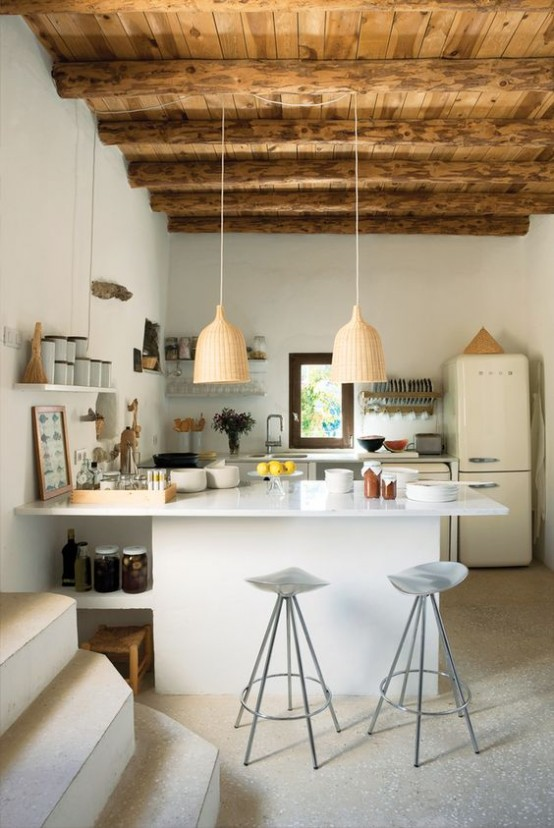 a modern white kitchen with an oversized white kitchen island, a wooden ceiling with beams for a warm and cozy feel and pendant woven lamps