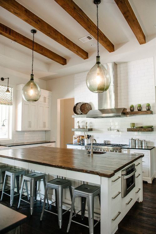 a white kitchen with chic farmhouse cabinetry, a large kitchen island, pendant lamps, rich-toned wooden beams that add coziness to the space