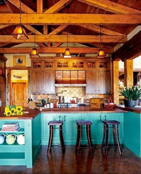 a bright kitchen with wooden upper cabinets and turquoise lower ones, rich-toned wooden beams with pendant lamps for a more catchy and vintage look