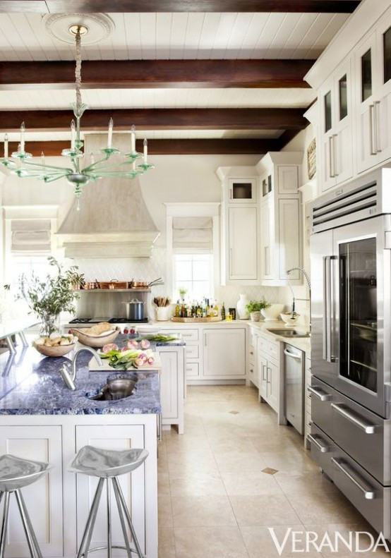 an elegant white vintage kitchen with chic cabinetry, a large kitchen island, chic stools, dark wooden beams for a refined feel and a creative glass chandelier