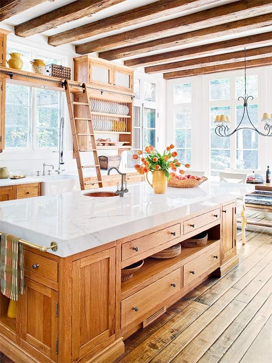 a warm-colored farmhouse kitchen with rich-colored cabinetry, white marble countertops, wooden beams on the ceiling and a vintage chandelier