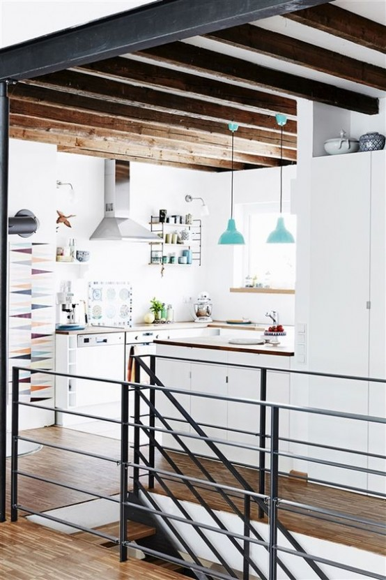 a minimalist white kitchen with sleek cabinetry, wooden countertops, wooden beams for a warm touch and blue pendant lamps looks cool and chic