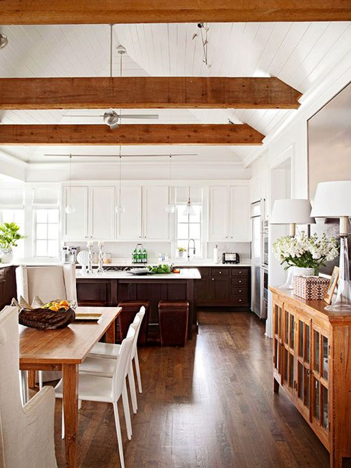 a modern two-tone farmhouse kitchen with upper white and lower dark cabinets, rich-tone wooden beams and pendant lamps that highlight the attic ceiling