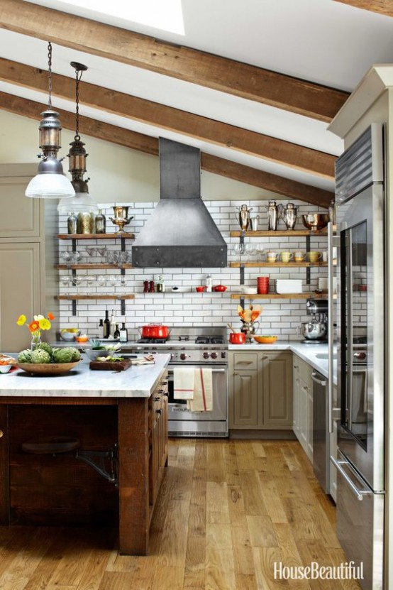 a cozy farmhouse kitchen with neutral cabinetry and stainless steel appliances, a dark heavy kitchen island, wooden beams that highlight the attic ceiling and vintage lamps hanging on them