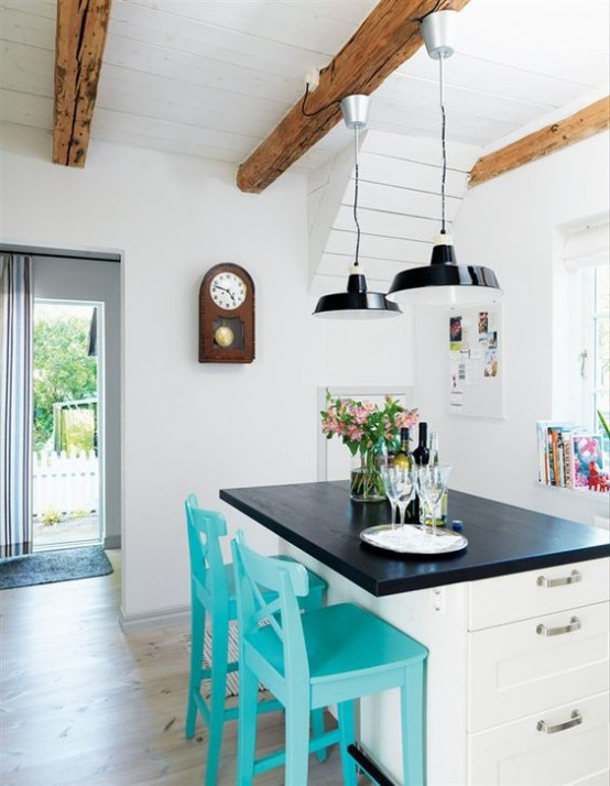 a white farmhouse kitchen with cozy white furniture, black pendant lamps and wooden beams that add interest and warm to the clean and airy space