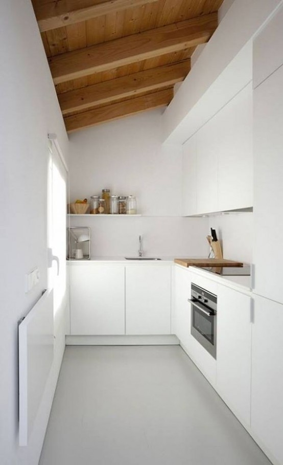a minimalist white kitchen with sleek cabinetry, a wooden ceiling with wooden beams that softens and warms up the space and brings interest to it