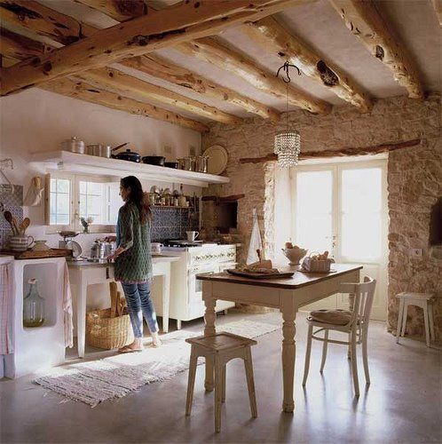 a French farmhouse kitchen with stone walls, exposed wooden beams and vintage white furniture and a crystal chandelier
