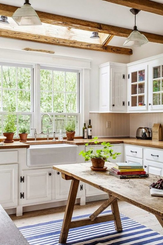 a white farmhouse kitchen with wooden countertops, a wooden table kitchen island and wooden beams that cozy up the kitchen