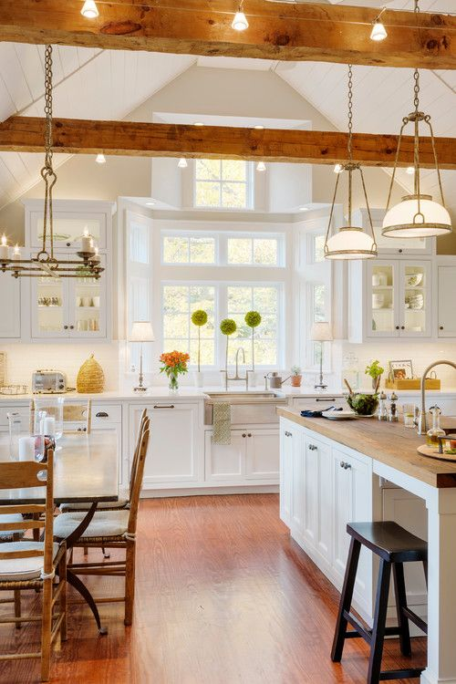a white modern farmhouse kitchen with chic cabinetry, wooden beams with lights and elegant chandeliers and lamps