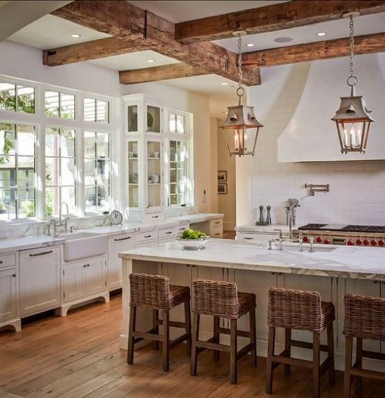 a neutral and refined kitchen with white cabinetry, wooden beams with elegant lamps and woven stools that add chic and coziness here