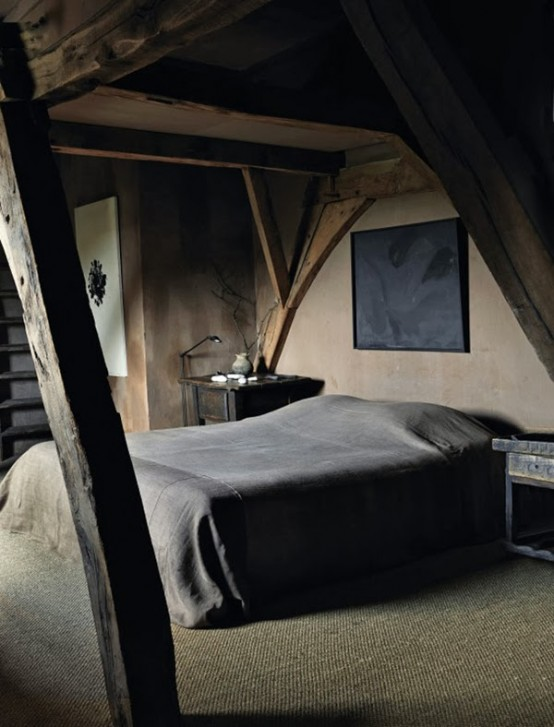 a moody bedroom in wabi-sabi with wooden beams, rough wooden nightstands and artworks