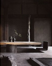 a wabi-sabi living room with rough stone walls, floor and a rough wooden low table is pretty moody