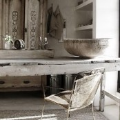 a rough wooden table, a rough stone bowl and a shabby metal chair add a touch of wabi-sabi aesthetics to the space