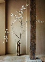 a rough concrete vase and a rough wooden beam add to the space and make it more wabi-sabi
