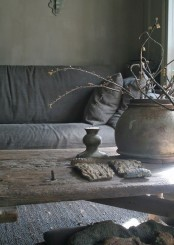 a rough wooden table, a porcelain vase with branches, coarse fabric and some other elements to create a wabi-sabi interior