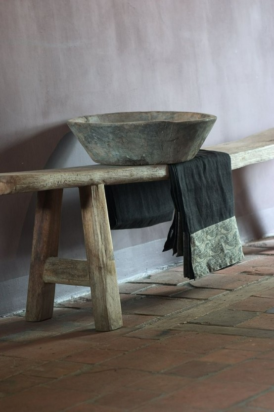 a rough wooden bench and a stone bowl plus a simple blanket for a wabi-sabi bathroom