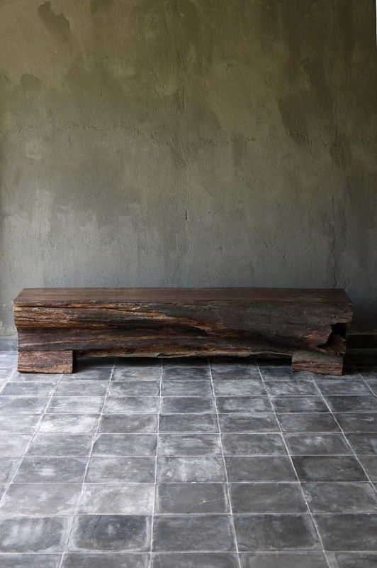 shabby tiles on the floor and a concrete wall plus a rough wooden slab bench for a wabi-sabi entryway