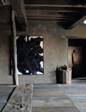 a wabi-sabi living room covered with rough wood, planks, beams, artworks and a basket for storage