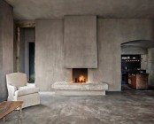 a wabi-sabi living room with concrete walls and a fireplace, a matching floor and very few furniture pieces