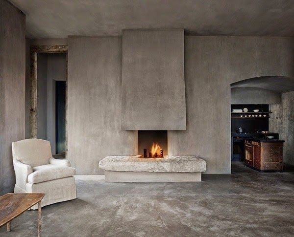 a wabi sabi living room with concrete walls and a fireplace, a matching floor and very few furniture pieces