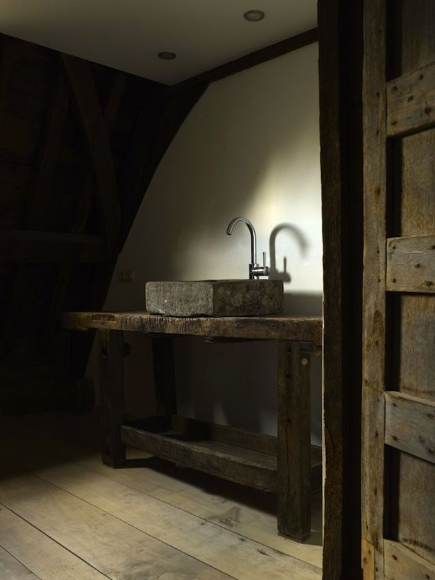 a wabi sabi bathroom with a wooden vanity, a stone sink and bare walls for a minimalist and rough look