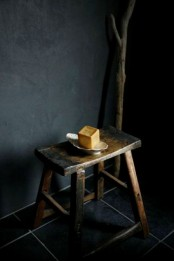 a simple matte black wall of painted concrete, a burnt wooden stool and a wooden stick for a natural and wabi-sabi look