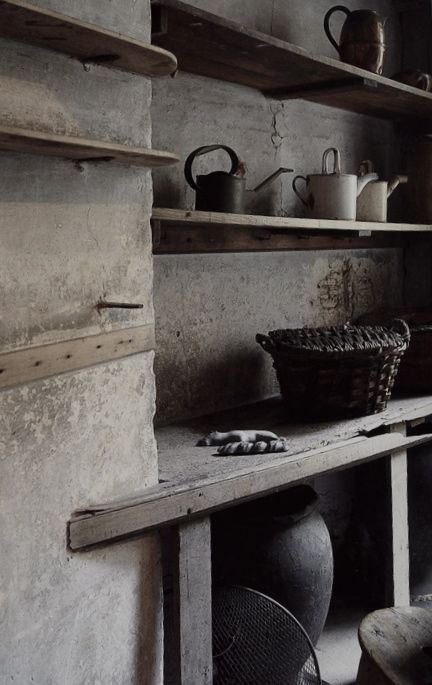 a wabi-sabi pantry in wood and stone, with baskets and buckets, a large vase for storage