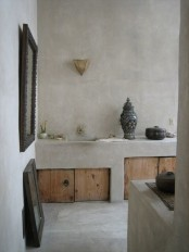 a concrete kitchen with built-in furniture with wooden doors and vintage details and decor
