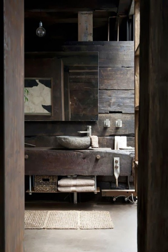 a wabi-sabi bathroom with a rough wooden wall, a rough wooden vanity and a stone sink