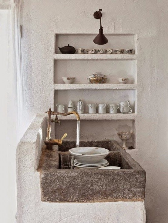 a wabi-sabi kitchen with rough white concrete walls, built-in shelving and a stone sink looks unusual and cozy