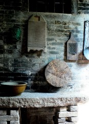 a kitchen in wabi-sabi style, with cutting boards, bowls and buckets and a hearth
