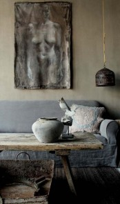 a wabi-sabi living room with a pendant lamp, an artwork, a rough wooden coffee table and a metal bathtub