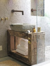 a wabi-sabi bathroom with a wooden console, white stone walls and a matching sink plus metal fixtures