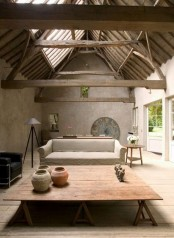 a cozy living room with a wabi-sabi feel – rough concrete walls, a wooden roof and beams