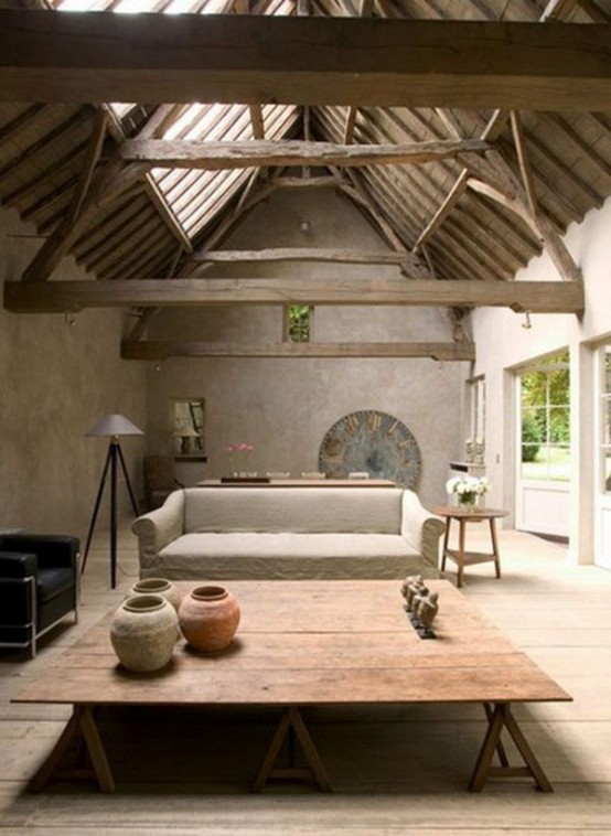 a cozy living room with a wabi-sabi feel - rough concrete walls, a wooden roof and beams