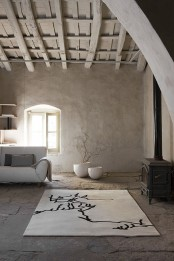 a neutral living room with a wooden roof and beams, a rough stone floor, rough concrete walls and minimal furniture