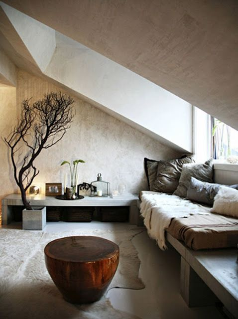 a minimalist meets wabi-sabi living room with rough stone walls and a wooden bench, faux fur and pillows
