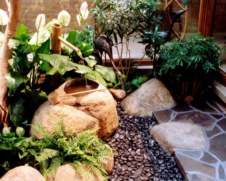 a mini Japanese garden with dark pebbles, a traditional bamboo fountain, large rocks, greenery and ferns