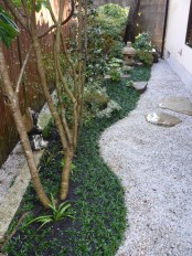 a Japanese garden with grass, pebbles, greenery, low trees and stone lanterns plus flat rocks