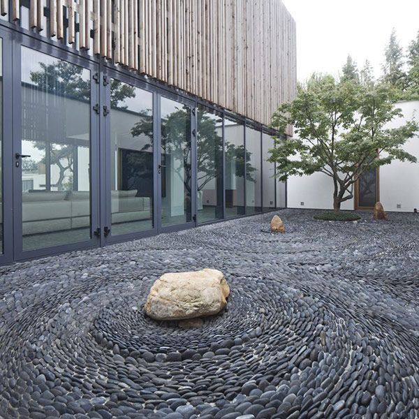 a Japanese rock garden composed of pebbles and rocks, with a single tree accented