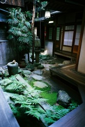 a Japanese backyard with moss, ferns, rocks, stone lanterns and a low tree for a calming and welcoming space