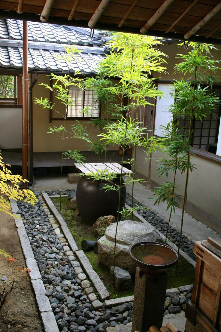 a Japanese courtyard with pebbles, rocks, moss, a large stone, a bowl with a bamboo cover and some greenery