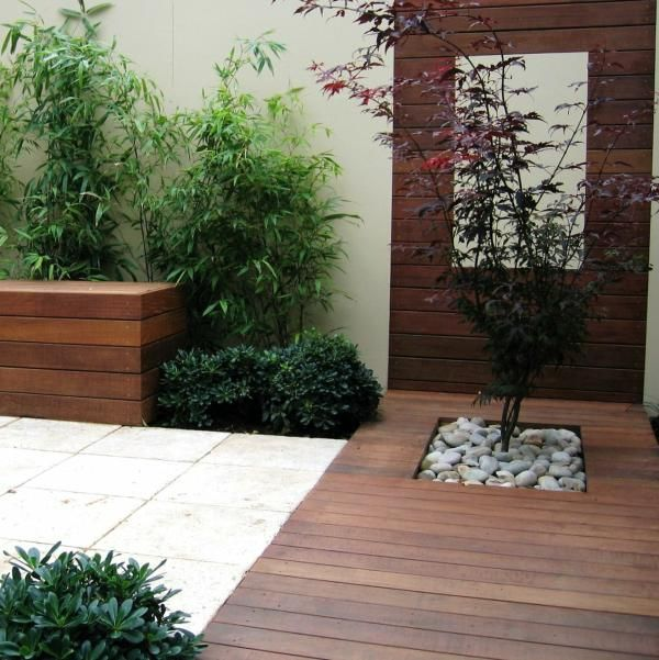 a contemporary wooden deck with a single tree with pebbles, greenery and a wooden wall