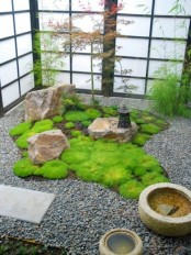 a Japanese courtyard with pebbles, rocks, stone bowls, a lantern and greenery around