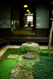 a Japanese garden with greenery and moss, rocks and pebbles and some bamboo