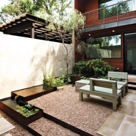 a contemporary backyard with a Japanese feel and a series of ponds with greenery, leaves and a tree next to them