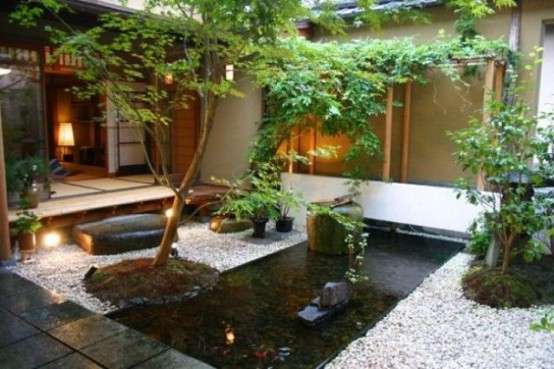 a beautiful Japanese backyard with a stone covered space, a pond in the center and rocks and trees plus greenery